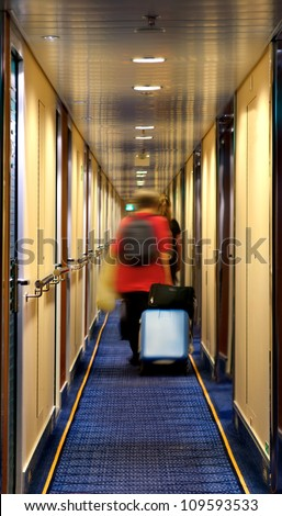 Blurred people with suitcase in hotel corridor