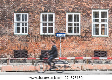 Blurred person going by bike in Copenhagen with a brick wall on background with white windows and a one way road sign. Focus on the wall. - stock photo