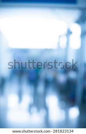 Blurred photo of an airport terminal with unrecognizable passengers passing by with luggage. Blurred background for topics of travel and transportation. - stock photo