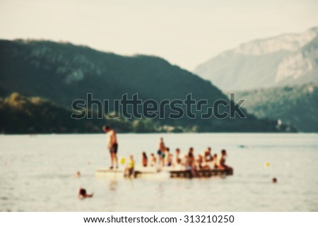 Blurred photo of Annecy lake (France). Adults and kids relax on rubber floating raft  at the Annecy lake surrounded by beautiful mountains. Toned photo. - stock photo