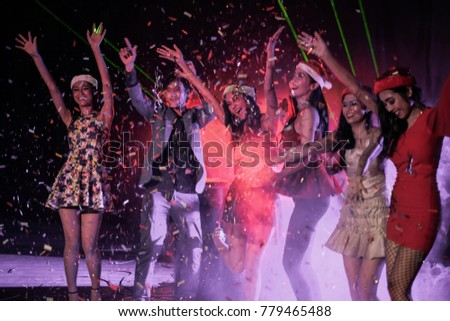 Blurred photo of christmas party. Group of beautiful happy man and women at celebration party with confetti falling everywhere on them. Christmas eve or New Year eve celebrating concept.