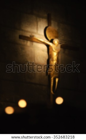 Blurred photo of crucifix on the stone wall and the candles at foreground. Symbolic contrast of light and darkness.  - stock photo