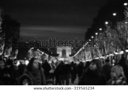 Blurred photo of people promenade at Champs Elysees with Christmas festive illumination and Arch of Triumph seen at background. Paris in winter. Aged photo. Black and white.