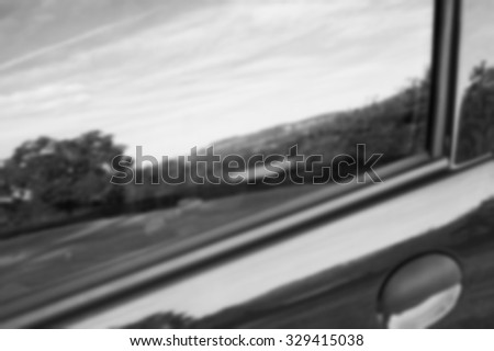 Blurred photo of rural landscape reflected in side window of a car. Black and white photo. - stock photo