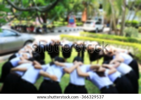 Blurred photo of students in university making circle cheers