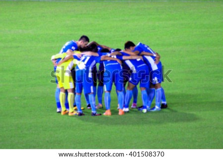 Blurred photo of Thai soccer players which has strategy discussion - stock photo