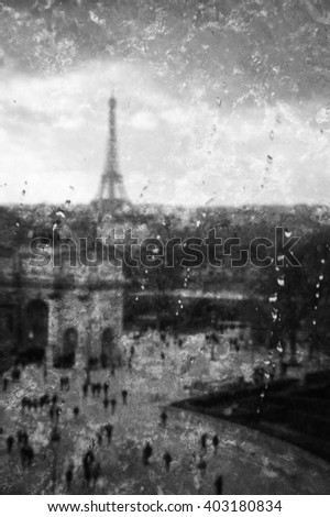 Blurred photo of view from wet window Arc de Triomphe at the square of Carrousel (near Louvre museum) and Eiffel tower at sunset in rainy day. Retro aged stained photo with scratches. Black and white. - stock photo