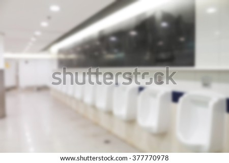 Blurred photo of white urinals in men's public restroom. department fixture indoor line luxury perspective piss rest stall store tiled wash - stock photo