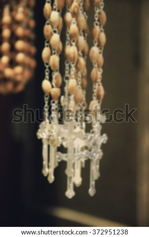 Blurred photo of wooden rosary beads with silver crucifix.