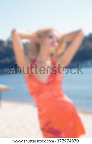 blurred photo sexy fashion girl blonde in red dress  on the beach