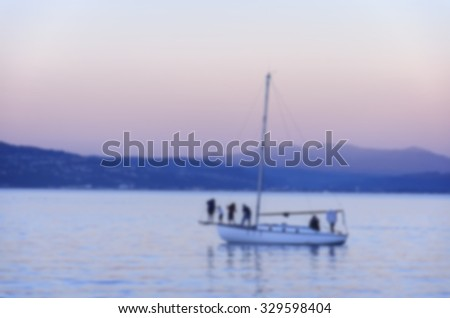 Blurred photo with people enjoy the sunset on a sailboat in the ocean harbor in Wellington, New zealand