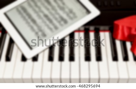 Blurred piano keyboard, red silk ribbon and tablet with musical notes.