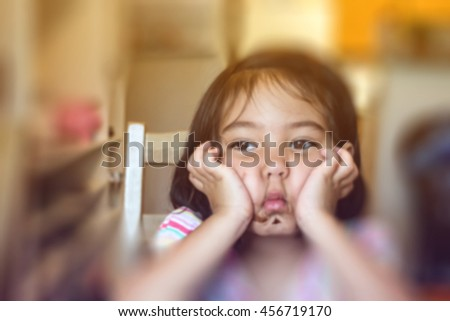 blurred picture of a cute little girl getting messy while eating chocolate and making sad face in dining room , filtered color tone - stock photo