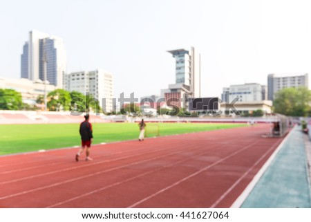 Blurred picture of Athletes running on the red running track in athletics stadium. - stock photo