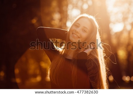 Blurred picture of beautiful lady standing in the warm rays of evening sun