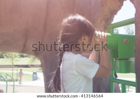 Blurred picture of  little girl looking through telescope at playground, vintage filtered color tone