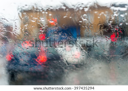 Blurred picture of traffic through a car windscreen during heavy rain. - stock photo
