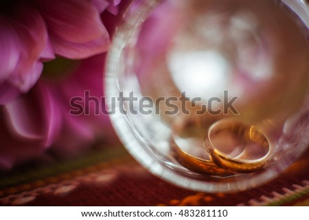 Blurred picture of wedding rings lying in the glass bowl