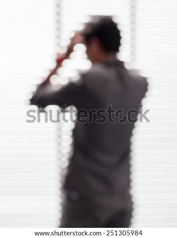 Blurred picture of young businessman in office is forced by under pressure from competitors. - stock photo
