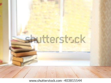 Blurred pile of books. Books on the window. Books with wooden background - stock photo