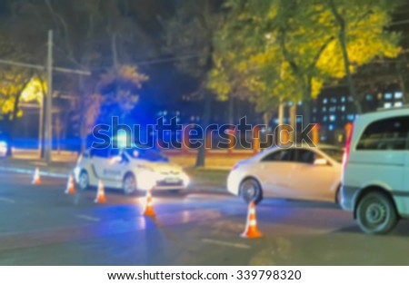 Blurred police car on the street at night. Orange cones set up to direct traffic around a police car in the collision scene. Great background blur                                - stock photo