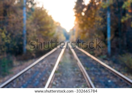 Blurred railway in the autumn forest. Travel background.