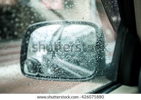 blurred rain drop on car window in rainy day in blue color tone