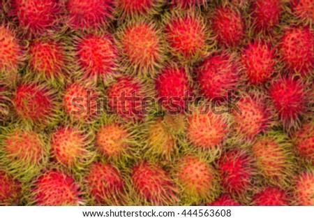 Blurred rambutan background. Sweet rambutan many delicious fruit in the market . rambutan sweet delicious fruit. background of fresh Thai rambutans.  rambutan  for sale. - stock photo