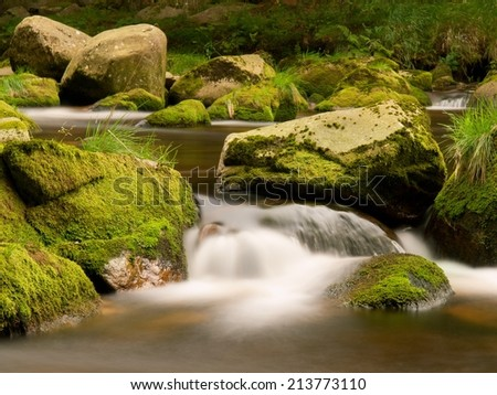 Blurred rapids of autumn mountain river, big mossy boulders obstruct water in motion,  bubbles create milky foam.  - stock photo