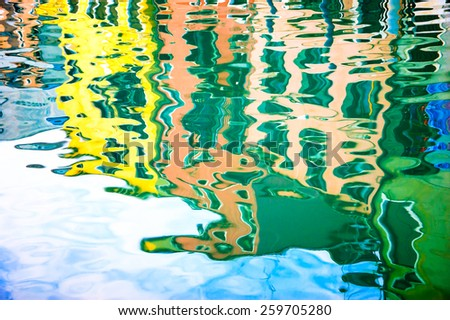 Blurred reflection of colorful houses on the water. Venice, Italy. Blurred abstract background. - stock photo