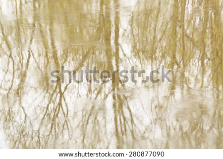 Blurred reflection of trees and sky in a small wood river. Spring. The concept of outdoor recreation.