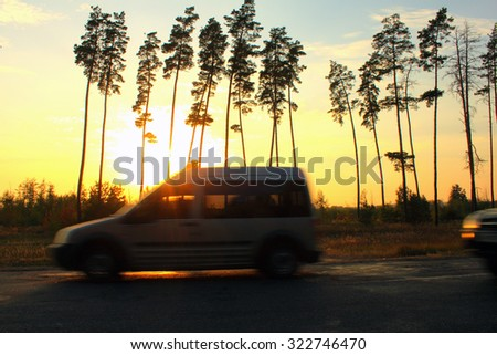 Blurred road and car against the backdrop of beautiful sunset and trees, speed motion  - stock photo