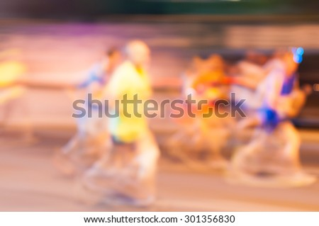 Blurred runner athlete running at night marathon. Man fitness silhouette evening jogging workout wellness concept - stock photo
