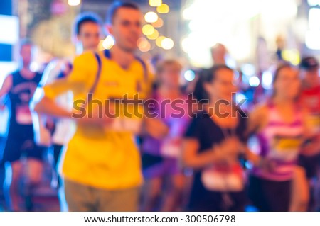 Blurred Runners shortly after the start at the night run.  Bokeh background. - stock photo