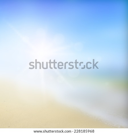 Blurred sandy beach backdrop with turquoise water and bright sun light. Summer holidays concept - stock photo
