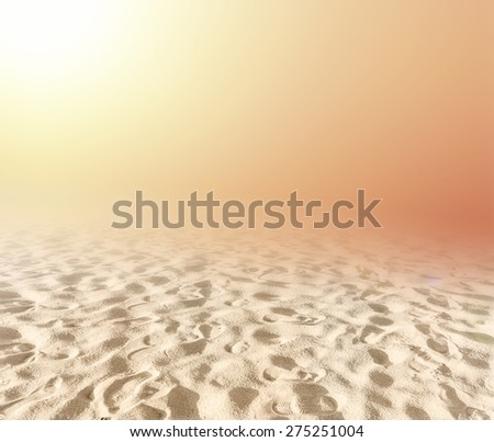 Blurred sandy beach backdrop with turquoise water and bright sun light. Summer holidays concept. - stock photo