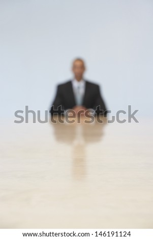 Blurred shot of a businessman sitting at the end of conference table in office - stock photo