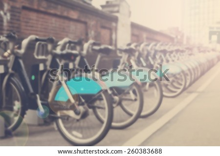 Blurred shot of bikes for rent in London, vintage filter applied, sunshine beams  - stock photo