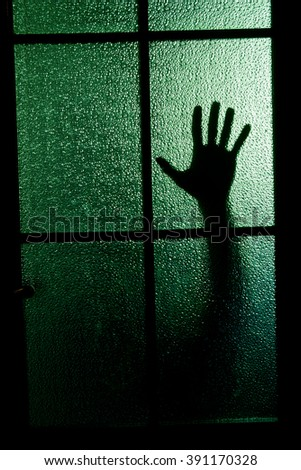 Blurred silhouette of a hand behind a window or glass door (symbolizing horror or fear) - stock photo