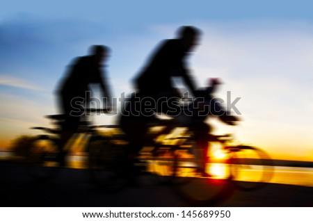 Blurred silhouette of four ( 4 )people - two couple Image of sporty company friends on bicycles outdoors against sunset. Silhouette A lot phases of motion couple of cyclist along the shoreline coast - stock photo