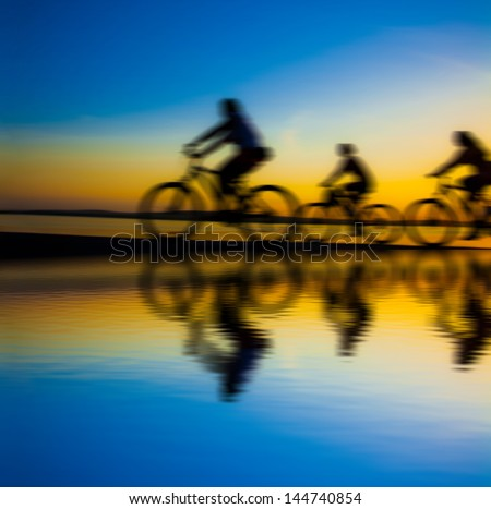 Blurred silhouette of people Image of sporty company friends on bicycles outdoors against sunset. Silhouette A lot phases of motion couple of cyclist along the shoreline coast - stock photo
