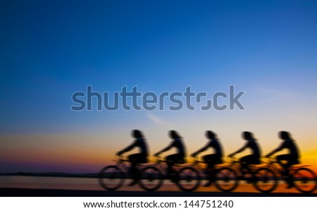 Blurred silhouette of people Image of sporty company friends on bicycles outdoors against sunset. Silhouette The four phases of motion of a single cyclist along the shoreline coast - stock photo