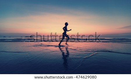 Blurred silhouette of woman running on sea beach at dusk.