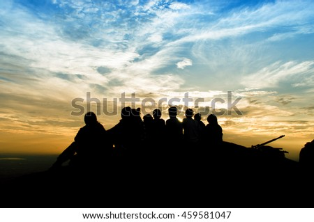 blurred silhouette woman on top mountain with color of sunset, low key