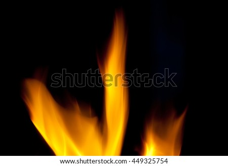 Blurred silhouettes of flames of fire in the dark (as an abstract background)