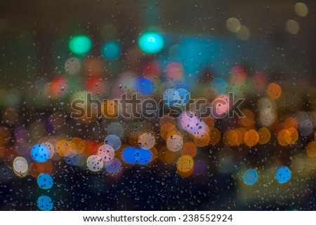 Blurred skyline lights with bokeh effect seen behind a wet window with raindrops. - stock photo