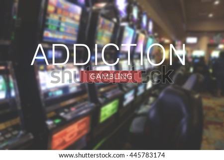 blurred slot machines in casino with gambling addiction text message - stock photo