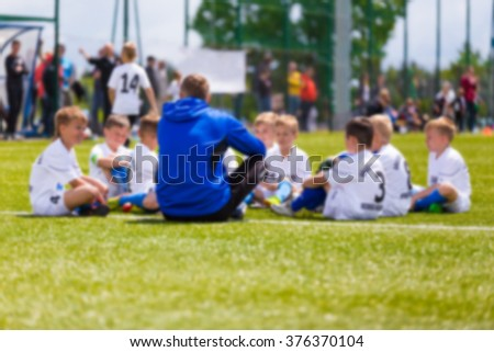 Blurred Soccer football background. Coach giving young soccer team instructions. Youth soccer team together before final game. Football match for children. Boys group shout team. Coach briefing. - stock photo