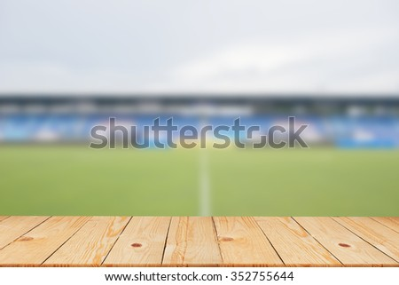 blurred soccer stadium in sunny day backgrounds with old vintage wooden desk tabletop,put and show your products on display or wallpaper