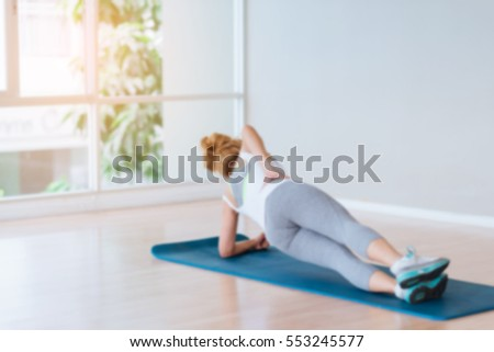 Blurred Sporty Girl are Side Planking for Weight Training Fitness - Sport and Lifestyle Concept